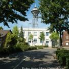 Verwaltungsgebäude mit Wasserturm und Pförtnerhäuschen (r.)